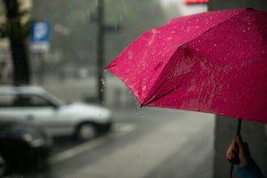 A person holding a pink umbrella under rain near a busy road.